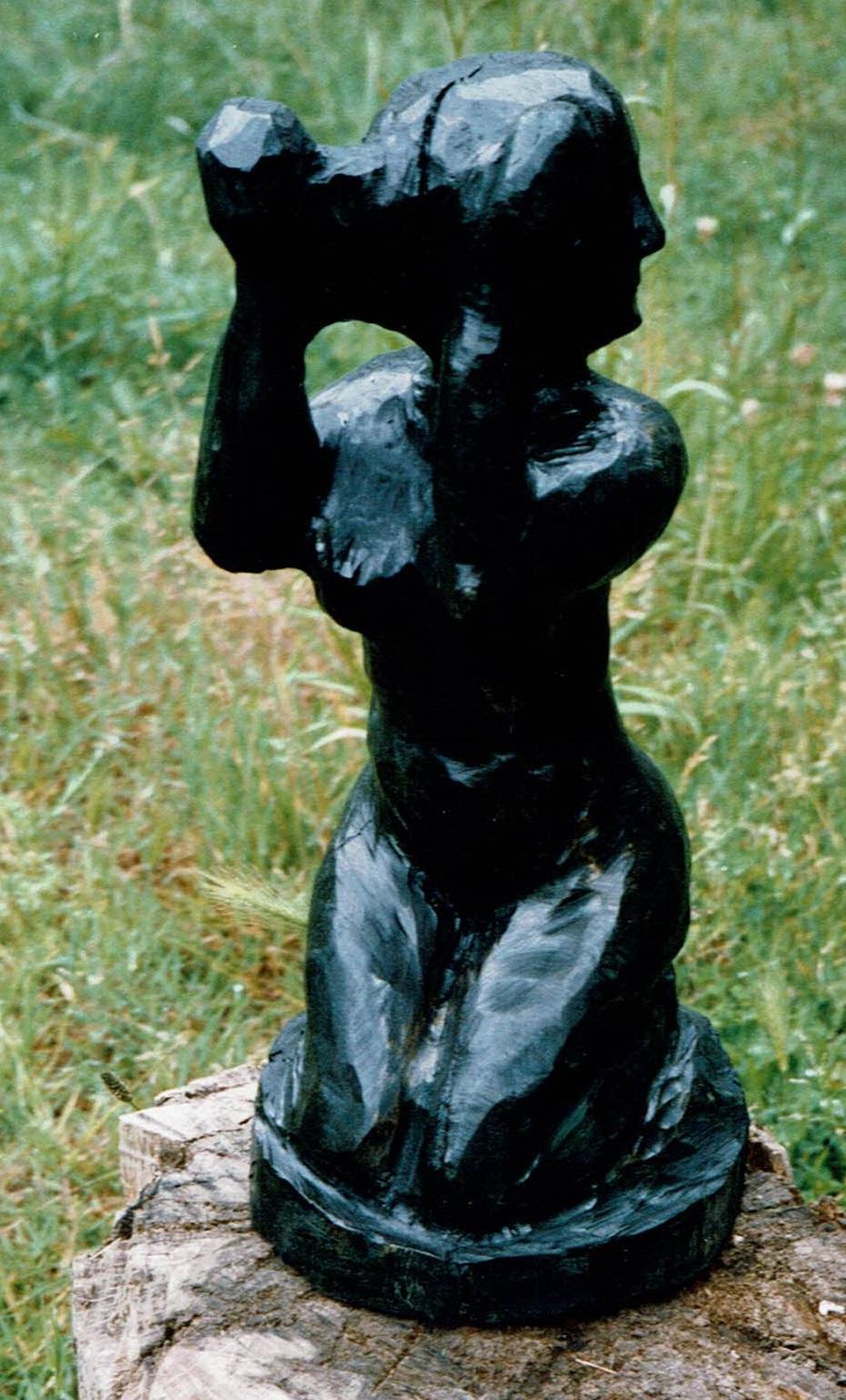 Figurine à genoux est conçue à partir d'acacia par Chris Le Guen
